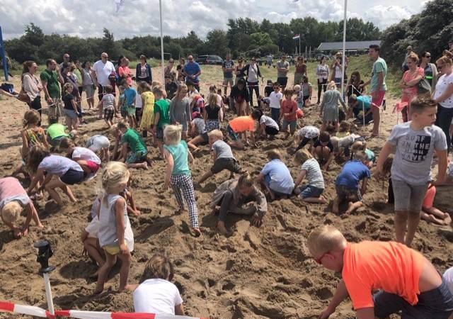 Kinderen op zoek naar schatten in het zand